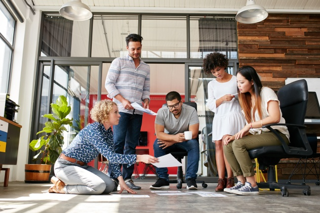 Designers planning layout on floor of office